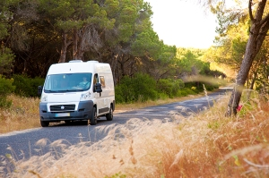 Campervan driving through trees on a isolated road